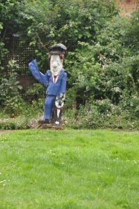 Postman Pat, one of many figures in a front garden, carved with a chainsaw.